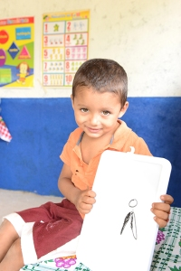 Joselito, holding his version of The Friends Project logo, during the first day of school at the preschool, 2014.
